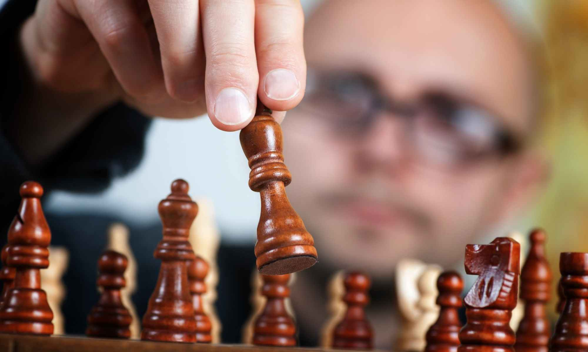 Shallow focus photography of white bald man holding brown chess piece over chess board