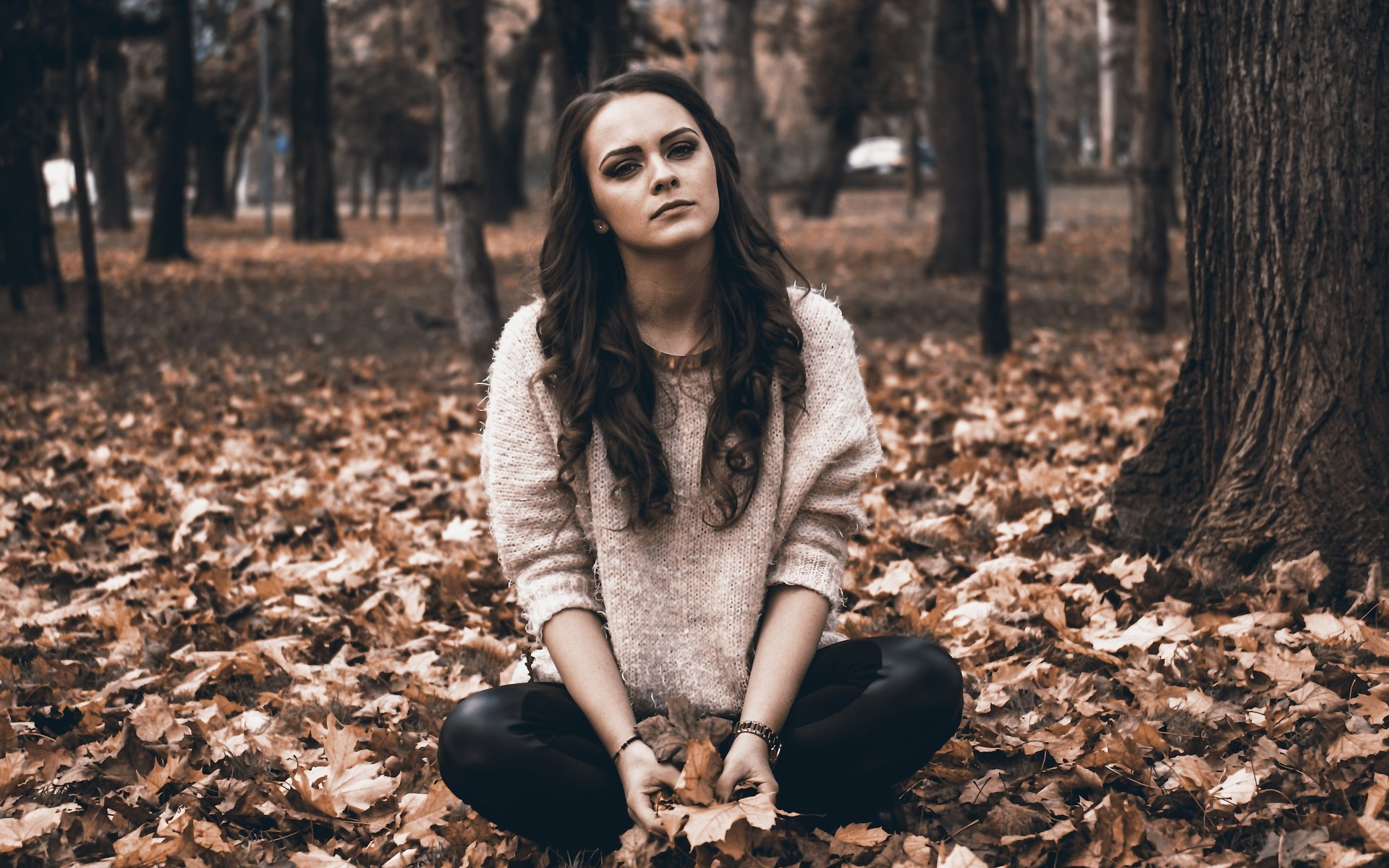 Depressed white woman sitting on ground surrounded by leaves near trees