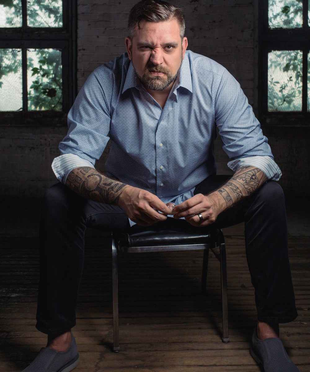 Angry white man with tattoos on arm sitting on black leather padded chair