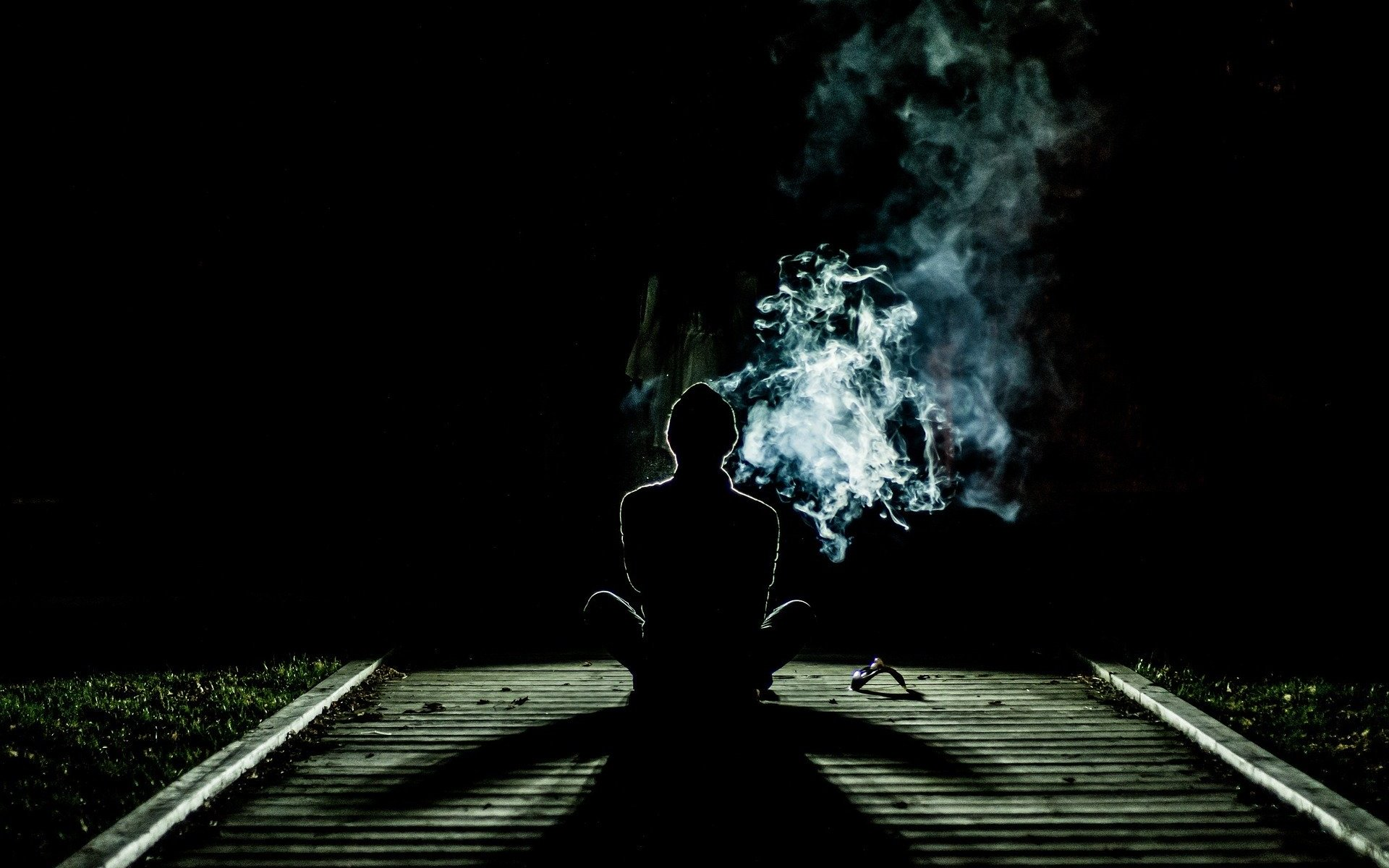 Person sitting on train track with cloud of smoke in the dark