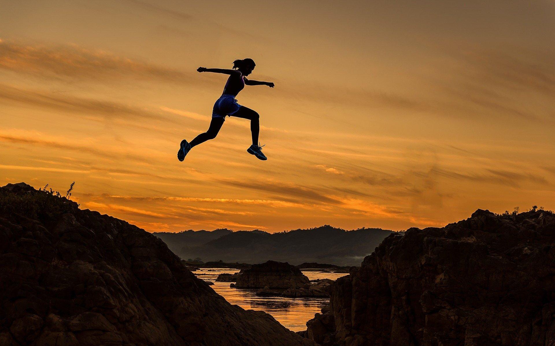 Female athlete jumping above ground near sunlit sky