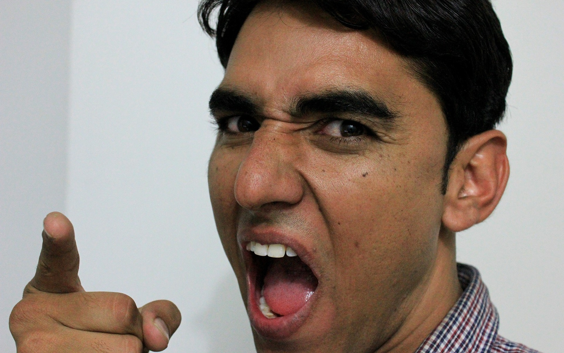 Angry brown Indian male pointing finger with open mouth