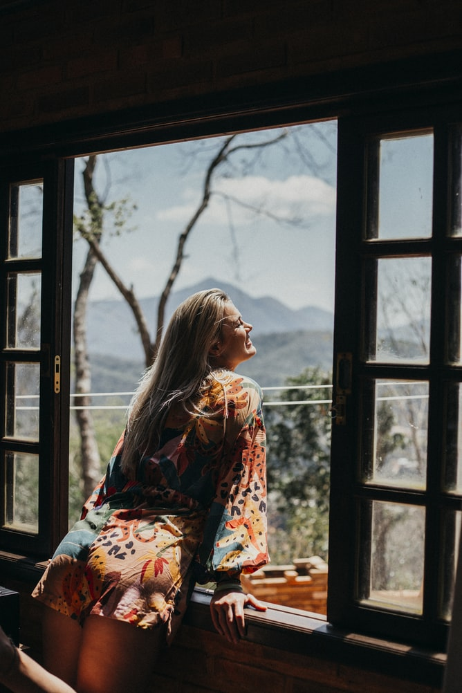 Attractive blonde woman standing next to open window looking outside