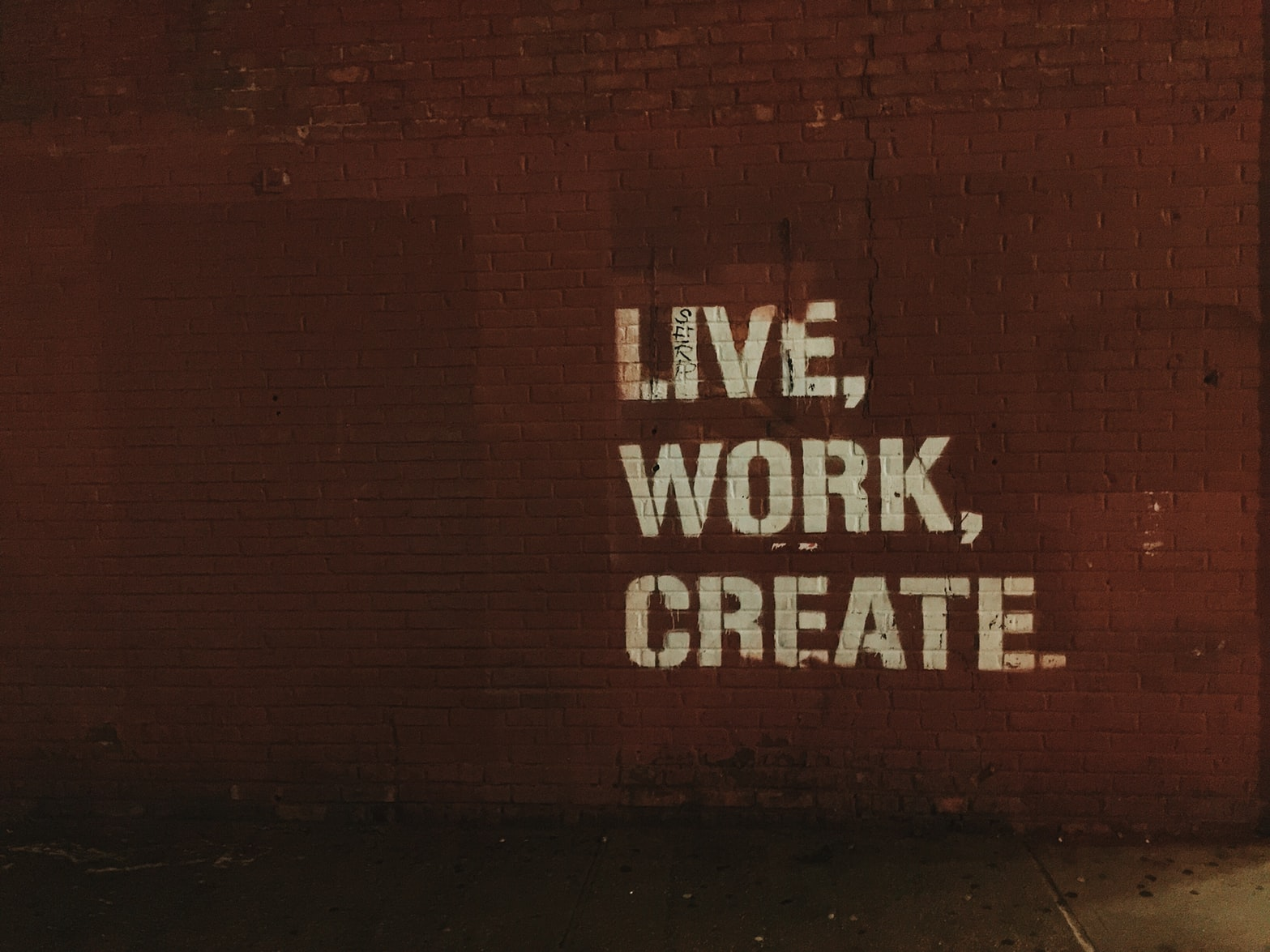 Red brick wall with live, work, create quote
