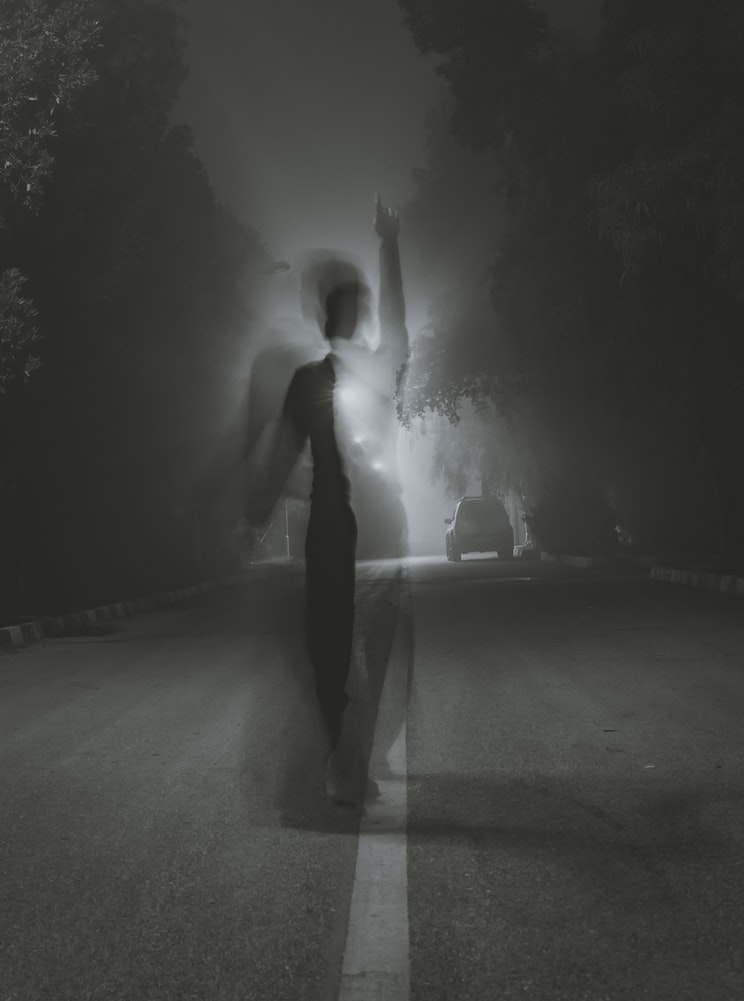 Man standing in middle of road at night