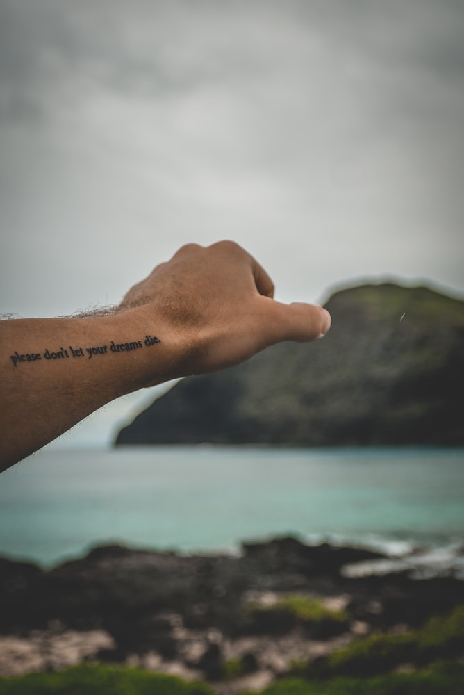 Close-up photography of arm with tattoo near body of water