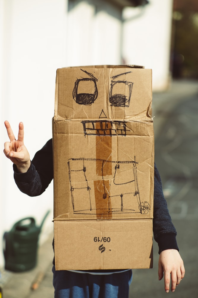 Person wearing brown cardboard box making peace sign