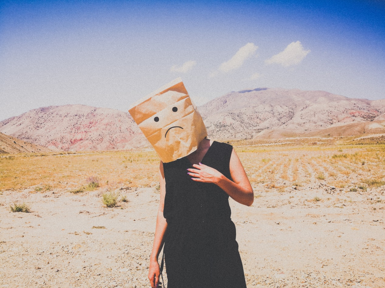 Woman in black dress wearing brown bag on head with sad face